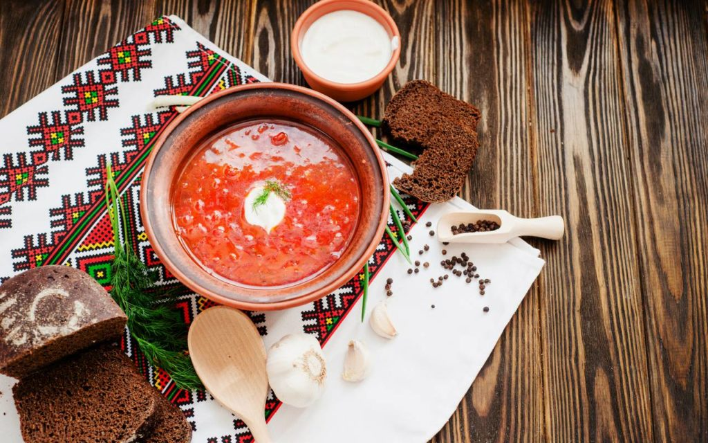 Borscht - one of the most popular Ukrainian dishes - presented in a bowl on a table and served alongside rye bread, garlic, and sour cream