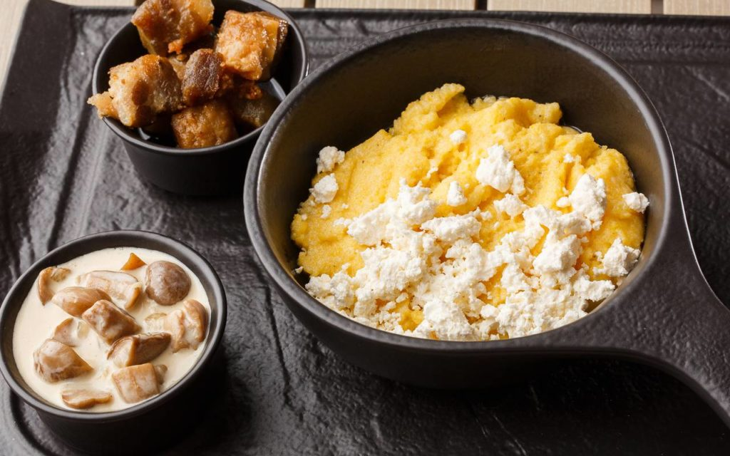 Ukrainian food - polenta or kulesha on a table in a bowl served with cheese and side dishes
