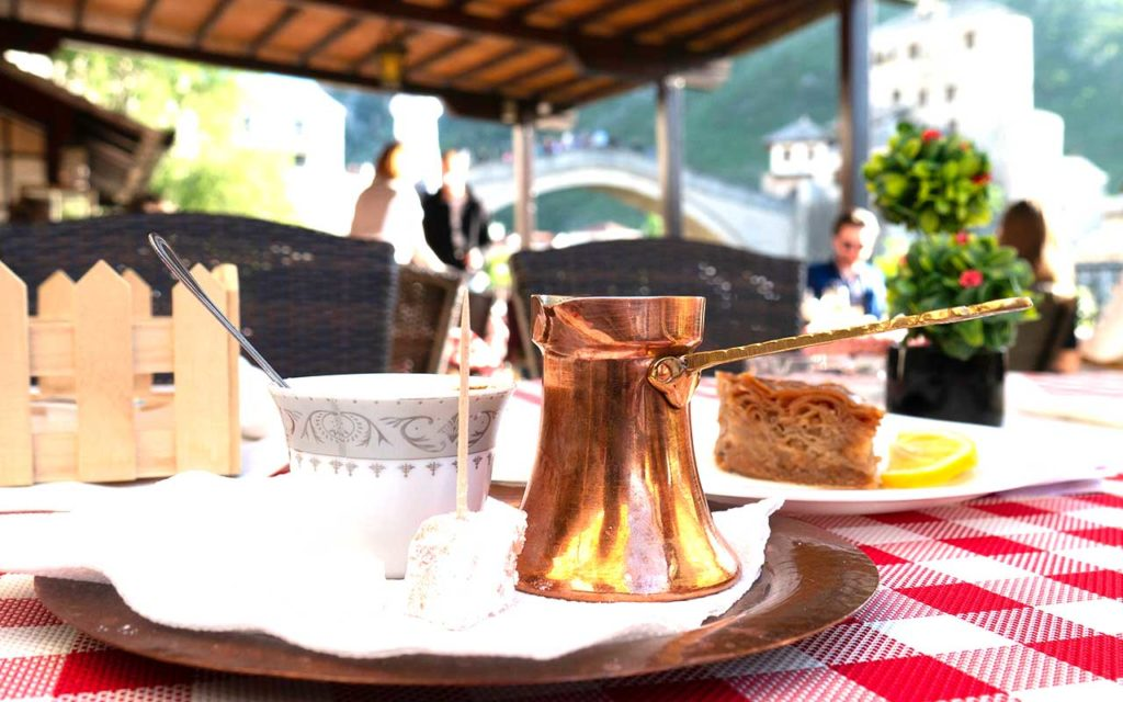 Traditional Bosnian coffee on the table with the view of Mostar Old bridge in the background