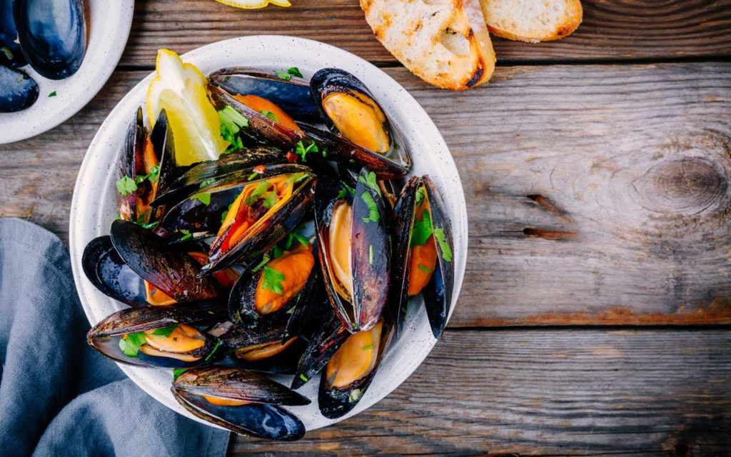 Welsh food: Conwy mussels with a slice of lemon and herbs in a white bowl on a wood table
