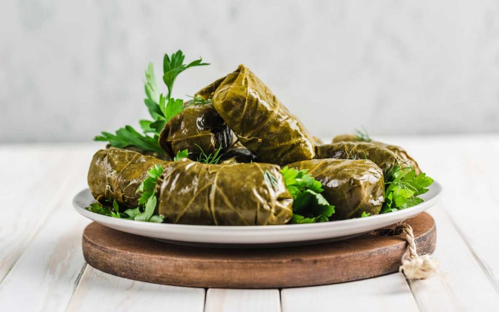 Mediterranean food: dolmas (delicious stuffed grape leaves on a plate with fresh cilantro on a wooden background)