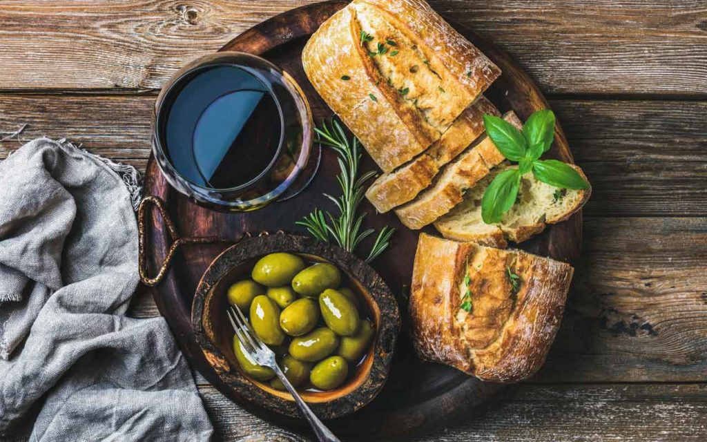 Bread, olives, wine on a wood background depicting the main elements of Mediterranean cuisine: olives, wheat, and grapes