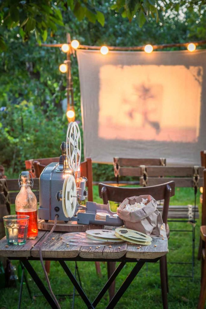 Staycation idea: backyard movie night with a projector, chairs, and popcorn