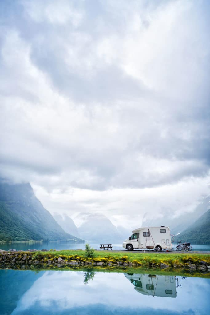 Staycation idea: an RV by a lake and mountains with beautiful scenery