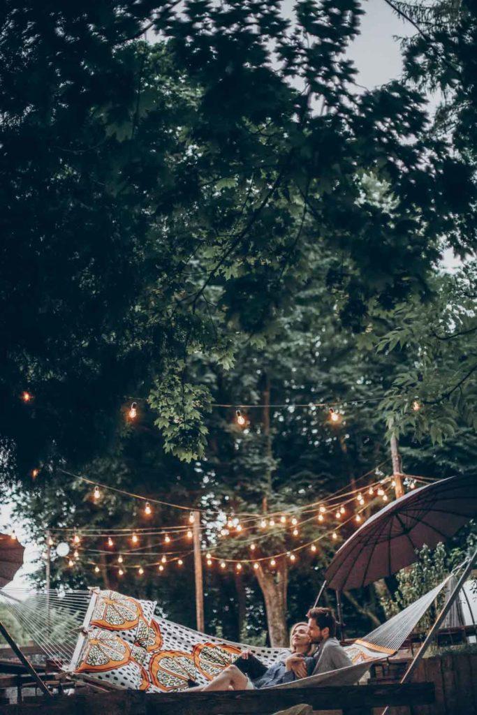 Staycation idea: a couple in a backyard oasis in a hammock
