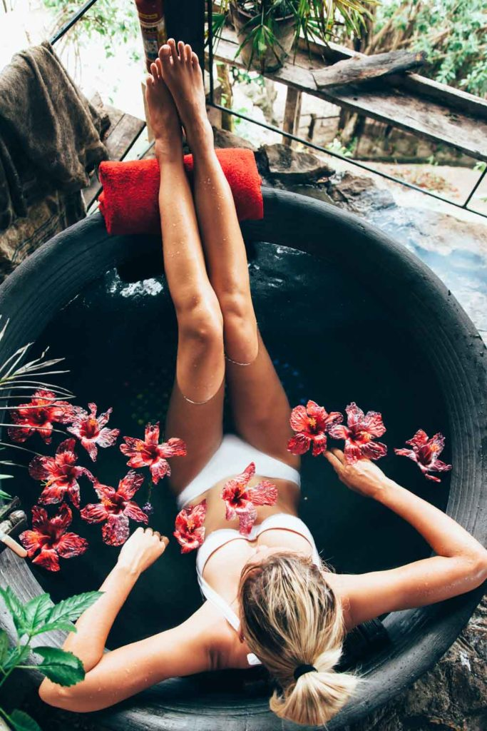 Staycation idea: taking a bath in a beautiful tub with flowers/petals floating in the water
