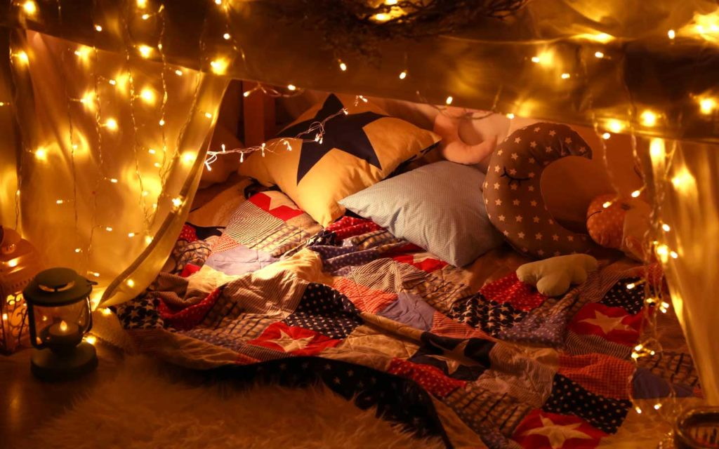 Staycation idea: a fort inside with beautiful string lights