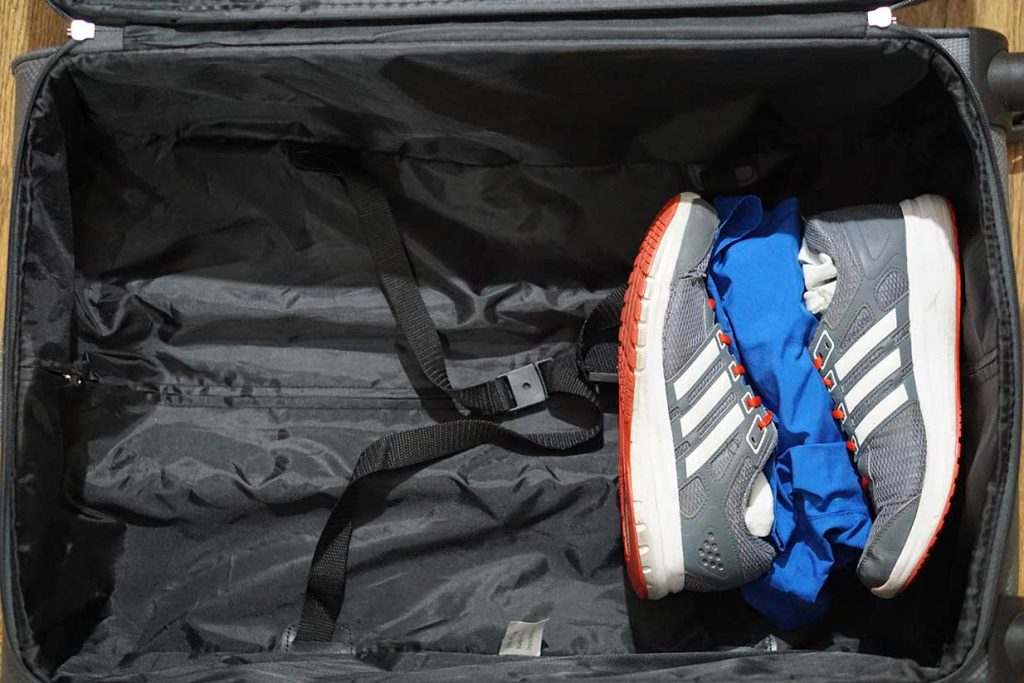 packing sneakers in a suitcase and layering