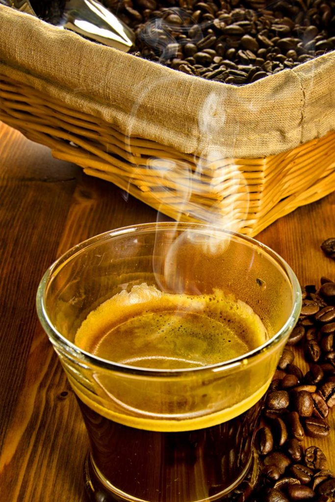Steaming coffee in a glass on a wodden board next to delicious-looking coffee beans
